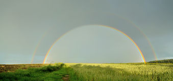 Panorama of double full rainbow over country road. Stock Images