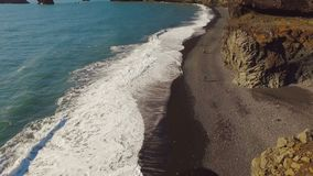 Panorama of Dyrholaey cape with black sand beach, waters of Atlantic ocean, basalt rocks. In sunny summer day stock video