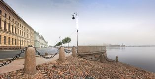 Dawn over Dvortsovaya Embankment and Neva in St. Petersburg. Panorama of early, foggy morning over Dvortsovaya Embankment and the Neva River in St. Petersburg royalty free stock image