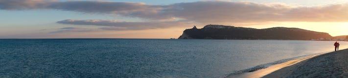 panorama eccellente della spiaggia principale di Cagliari (poetto sella del diavolo) con due amanti di camminata al tramonto sard immagine stock