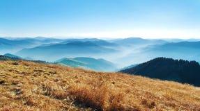 Panorama einer Ansicht der Hügel eines rauchigen Gebirgszugs herein umfasst Stockbilder