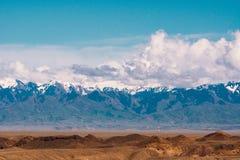 Panorama einer schönen Landschaft mit Bäumen und Feldern im Vordergrund und der Gebirgszüge mit Schnee-mit einer Kappe bedeckt in lizenzfreie stockfotografie