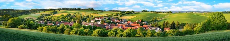 Panorama eines kleinen Dorfs umgeben durch grüne Hügel Lizenzfreies Stockbild