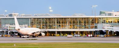 Panorama eines modernen Flughafens und der weißen Flugzeuge im elektrischen Licht beleuchtet Stockfotografie