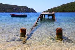 Panorama eines ruinierten hölzernen Piers und des alten Fischerbootes und der Berge im Hintergrund von sithonia Griechenland Lizenzfreie Stockbilder