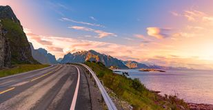 Empty road in Norway, Europe. Sunset travel. Panorama of empty winding country road in Norway, Europe, Scandinavia. Auto travel on sunset. Blue sky with clouds Royalty Free Stock Image