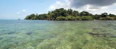 Panorama en las aguas bajas con una isla tropical Imagenes de archivo