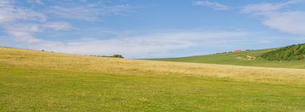 Panorama of an english countryside green valley. A green valley with a blue sky and a house on the background Royalty Free Stock Photos
