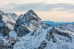 Panorama espectacular de la montaña del invierno con los picos cubiertos con nieve temprana imagen de archivo