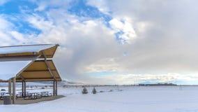 Panorama Expansief die landschap met onder sneeuw onder een bewolkte blauwe hemel in de winter wordt bedekt stock foto's
