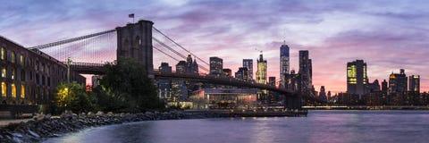 Panorama för Brooklyn bro och för Manhattan horisontsolnedgång arkivbild