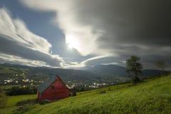 Panorama f?r berg f?r sommarnatt Stuga f?r litet hus p? brant berglutning p? dramatisk aftonhimmelbakgrund, ljus v?g med royaltyfri fotografi