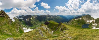 Panorama of Fagaras mountain ridge in summer. Beautiful view in to the valley of beautiful landscape with gorgeous cloudscape. rocky cliffs above the grassy royalty free stock photography