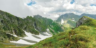 Panorama of fagaras mountain ridge in summer. Spots of snow on grass of steep slope. rocky tops. cloudy weather. romania landscape stock images