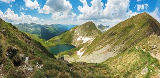 Panorama of fagaras mountain in summer. Glacier lake capra between hills. beautiful landscape with steep slopes, grassy meadows and peak. wonderful weather royalty free stock images