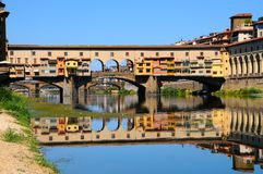A Beautiful view of the famous Old Bridge Ponte Vecchio and Uffizi Gallery with blue sky in Florence as seen from Arno river Royalty Free Stock Photos