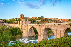 Panorama of famous Toledo bridge in Spain, Europe. Beautiful landscape of Toledo in Spain. Stone bridge across calm river. Blue sky reflected in crystal clear Royalty Free Stock Photo