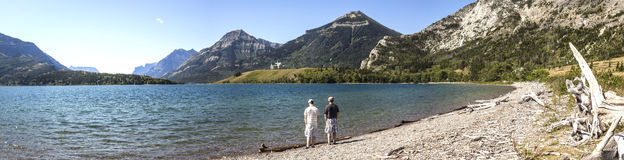 Panorama of father and son standing by lake with mountains in background. Panoramic image of Waterton National Park with father and son standing at the edge of Stock Images