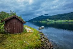 Panorama of fjord in Norway. Panorama of fjord with fisher house and white boat in Norway Royalty Free Stock Photos