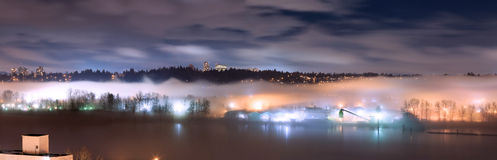 Panorama of fog covering city and river at night Royalty Free Stock Photo