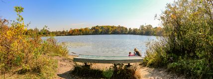 Panorama format landscape photo of a bench overlooking a lake with 2 people looking at the water. Beautiful Canadian. Fall weather stock photo