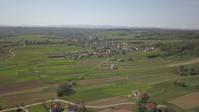 Panorama från en sikt för öga för fågel` s Centraleuropa: staden eller byn lokaliseras bland de gröna kullarna tempererat klimat  stock video