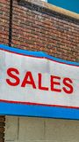 Panorama frame Close up of building exterior with a huge sign that reads Sales Service Parts. The old building has brick wall and the windows have white frames royalty free stock image
