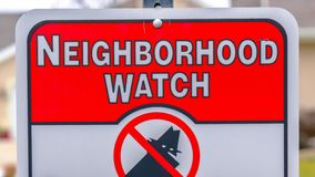 Panorama frame Close up of a Neighborhood Watch sign against a blurred background. The sign warns that all suspicious persons and activities are reported to stock image