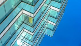 Panorama frame Close up of an office building exterior against blue sky on a sunny day. Roller blinds on the windows provide shade and privacy to the rooms royalty free stock photography