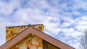 Panorama frame Close up of the roof of a house against trees and sky with cottony clouds. A colorful chimney protrudes from the roof of this house royalty free stock photo