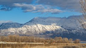 Panorama frame Construction site near a lake viewed on the other side of a white picket fence. A snow caapped mountain and cloudy sky can be seen in the royalty free stock photography