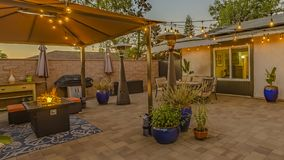 Panorama frame Cozy stone patio with string of lights over a covered seating and dining area. The house has a glass paned double door and window with view of stock photos