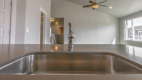 Panorama frame Glossy sink and faucet on the brown countertop inside a kitchen. The room is well lit by warm ceiling lights and the sunlight streaming through royalty free stock image
