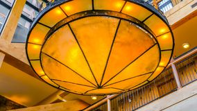 Panorama frame Gorgeous yellow round light hanging on the ribbed ceiling inside a building royalty free stock photos