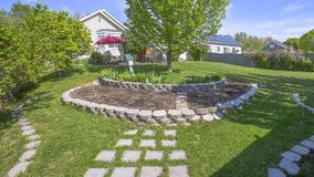 Free Panorama Frame Landscaped Grassy Yard Of Home With Lush Trees And Decorative Concrete Stones Stock Image - 154760471