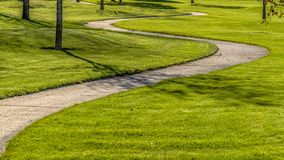 Panorama frame Pathway winding through a terrain with rich green grasses and young trees. The path leads to the road with view of mountain and sky in the stock photography
