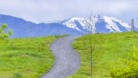 Panorama frame Paved pathways on a hill covered with vibrant green grasses. The snow covered peak of a mountain against cloudy sky can be seen in the distance stock photography