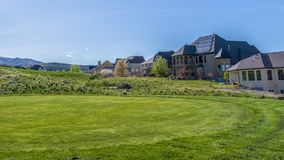 Panorama frame Residential houses on a terrain with vivid green grasses viewed on a sunny day. In the distance is a view of a mountain against pale blue sky stock photography