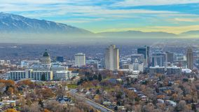 Panorama frame Utah State Capital Building and skyscrapers towering over the populous city. Snow capped mountain and cloudy blue sky can be seen in teh scenic royalty free stock images