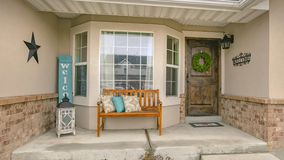 Panorama frame Welcoming porch of a home with brown bench in front of the half hexagon window. The stairs on the rocky yard leads to the rustic front door with stock images