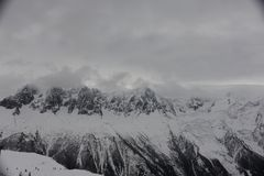 Panorama of French Alps with mountain ranges covered in snow and clouds in winter Royalty Free Stock Photo