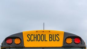 Panorama Front view of a yellow school bus with homes and cloudy sky in the background. Several side mirros and signal lights can be seen at the front of the royalty free stock photos