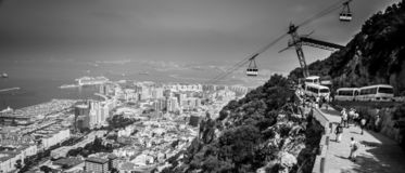 Panorama of Gibraltar. With `Rock of Gibraltar` and Gibraltar cableway and tourists buses in black & white royalty free stock photography