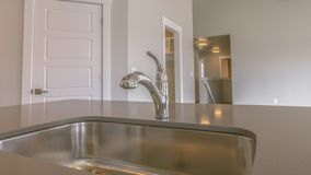 Panorama Gleaming stainless steel sink and faucet inside the kitchen of a new home. Warm celiling lights and a ceiling fan can also be seen inside the house royalty free stock images