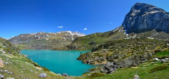 Panorama of Gloriettes lake. The ridge of Chourrugue is at right of the panorama with the reservoir lake Gloriettes, mountain chain of Heas Valley with the snowy Royalty Free Stock Photos