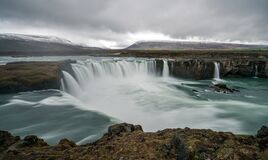 Panorama of Godafoss waterfall near Akureyri in the Icelandic highlands. Dramatic clouds and snow covered mountains in the back.