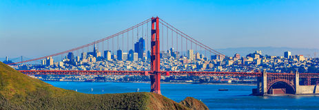 Panorama of the Golden Gate bridge and San Francisco skyline. Panorama of the Golden Gate bridge in clear blue sky with green grass as foreground and San royalty free stock photos