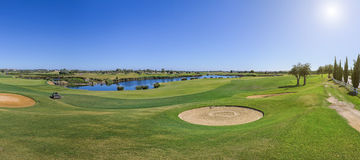 Panorama of a golf course on sunny day. Royalty Free Stock Image