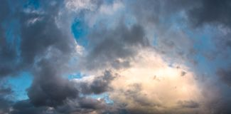 Panorama of gorgeous cloudscape at dusk. Heavy autumn clouds lit by the last rays of sun Royalty Free Stock Image