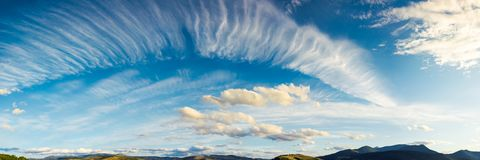 Panorama of a gorgeous cloudscape. Dynamic high cloud formations on a windy autumn day in mountains stock image
